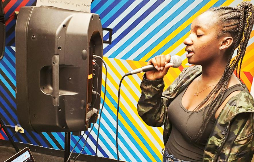 young woman singing into mic