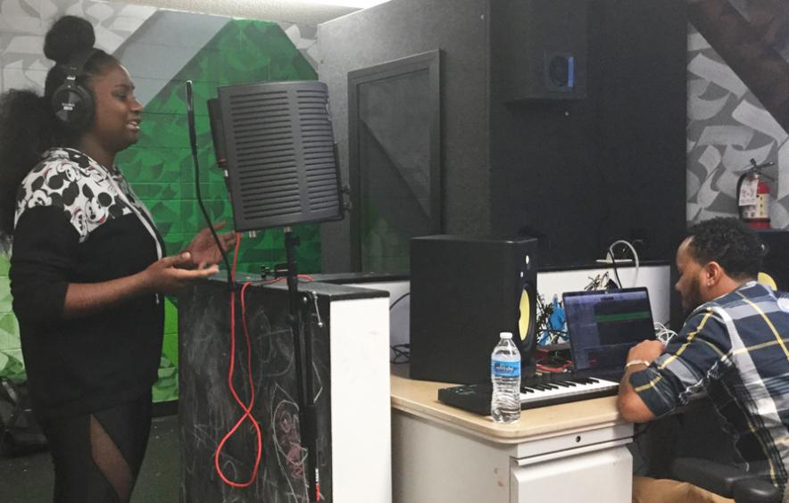 young black woman singing into mic at recording studio